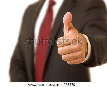 Close up of a corporate executive wearing a suit and tie giving the thumbs up sign selective focus - stock photo