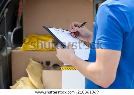 Close-up of a courier's hand writing on clipboard - stock photo