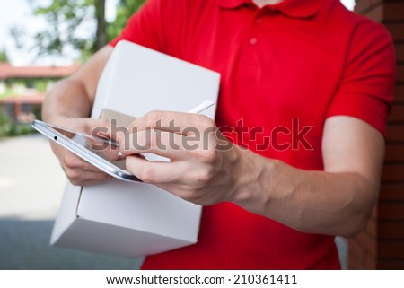 Close-up of a courier using tablet at work - stock photo
