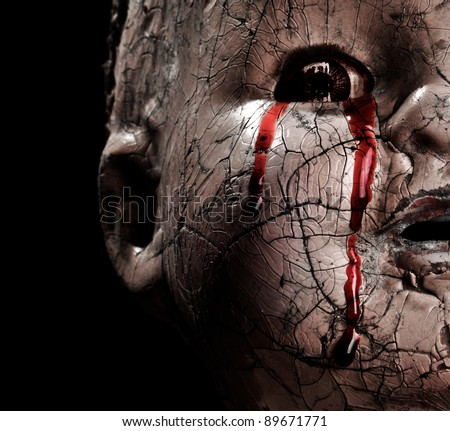 Close up of a Cracked Scary Doll Crying Blood in Horror - stock photo