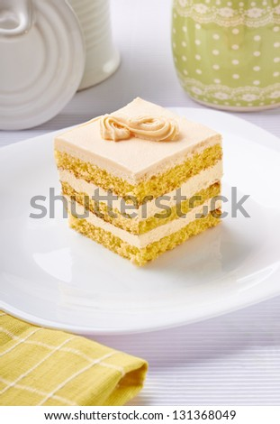 close up of a cream cake on white plate - stock photo