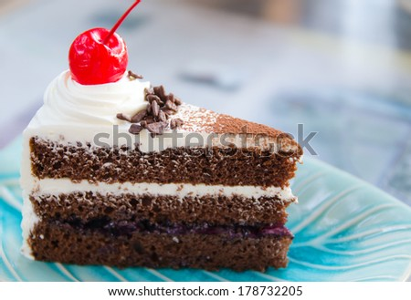 close up of a cream slice garnished with cherry on top served on a ...