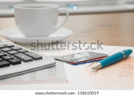 Close up of a credit cards,credit card statements and calculator with a cup of coffee in the background - stock photo