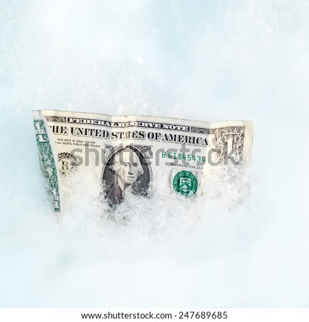 Close up of a crumpled dollar bill in a snow, business concept - stock photo