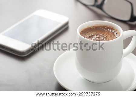 Close up of a cup of coffee on table with a smart phone and eye glasses - stock photo