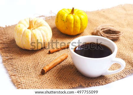 Close up of a cup of coffee with pumpkin and cinnamon on a sackcloth.