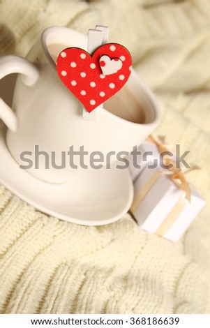 Close-up of a cup of coffee with small gift boxes and hearts - stock photo