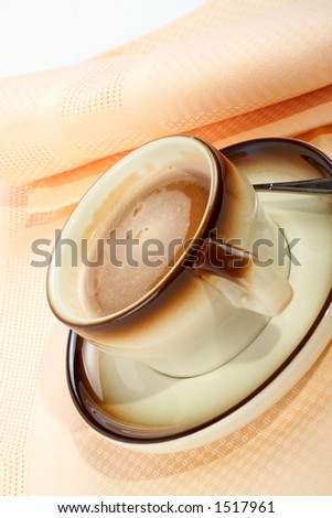 Close-up of a cup of coffee with the spoon, on ceramic plate
