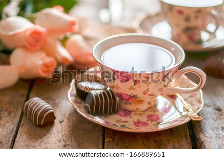 Close up of a cup of tea with roses and chocolate candies on wooden table - stock photo