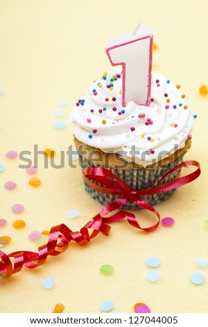 Close-up of a cupcake with candle and ribbon over plain background. - stock photo