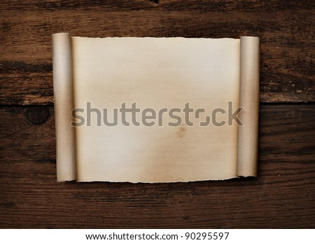 close up of  a curled paper on a wooden background