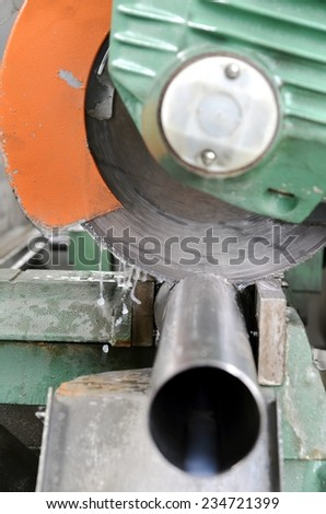 Close up of a cut of a piece of metal with a circular saw machine. Construction of a homemade muffler for sportive cars in stainless steel.  - stock photo