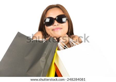 Close up of a cute Asian shopper smiling and wearing large stylish sunglasses while playfully embracing colorful department store bags, face, chin resting on hands. Thai national of Chinese origin - stock photo