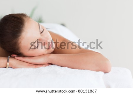 Close up of a cute brunette lying on a massage table in a spa