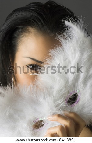 close up of a cute brunette with white feather mask