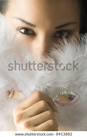 close up of a cute brunette with white feather mask and stunning eyes