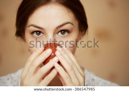 Close up of a cute brunette woman drinking tea at home
