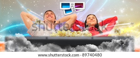 Close up of a cute couple watching movie on their home cinema station in their living room. Very realistic sound and vision like in true cinema - stock photo