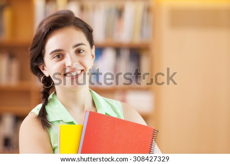 Close-up of a cute female student standing with notebooks at the library - stock photo