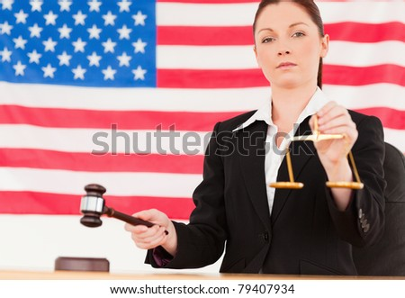Close up of a cute judge knocking a gavel and holding scales of justice with an American flag in the background - stock photo