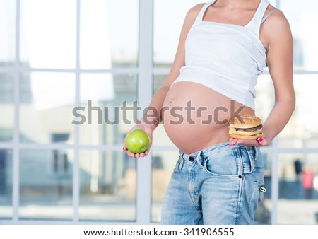 Close up of a cute pregnant belly tummy belly and healthy and unhealthy food. Pregnant female healthy motherhood concept. Side view, pregnant belly body part. New life third trimester - stock photo