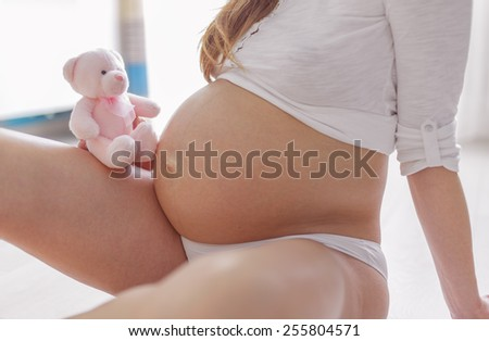 Close up of a cute pregnant belly with teddy bear - stock photo