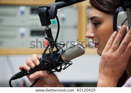 Close up of a cute singer recording a track in a studio - stock photo