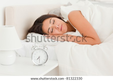 close up of a  cute woman sleeping under sheet in bedroom - stock photo
