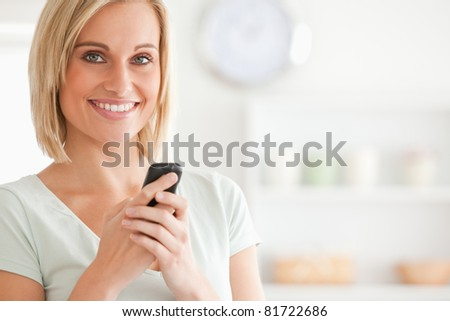 Close up of a cute woman with mobile looking into the camera in the kitchen