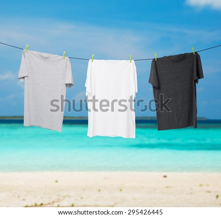 Close up of a dark grey, white and grey t-shirts on the rope. Tropical sand beach and ocean as background. - stock photo