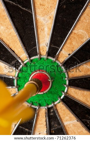 Close up of a dart that has nailed a bulls eye in the center of the dart board. Shallow depth of field. - stock photo