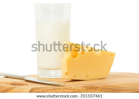 Close up of a delicious wedge of fresh cheese and  glass of milkon a wooden cheese board. Isolated on white. - stock photo