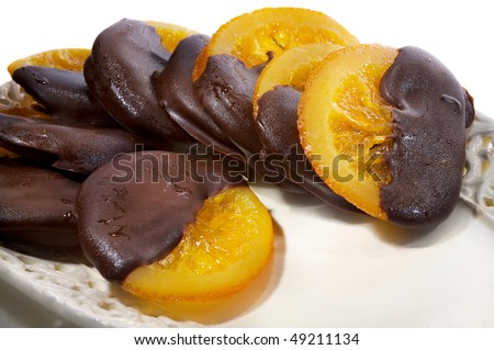 Close-up of a dessert from oranges covered with chocolate on a white plate - stock photo