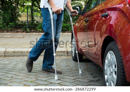 Close-up Of A Disabled Man With Crutches Walking Near Care - stock photo