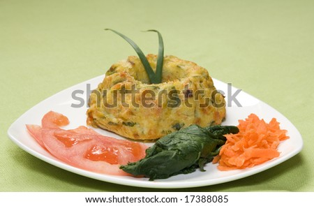 Close up of a dish with a vegetable quiche and salad. It has a clipping path. Focus starts to fade away from last border of the quiche to the background. - stock photo