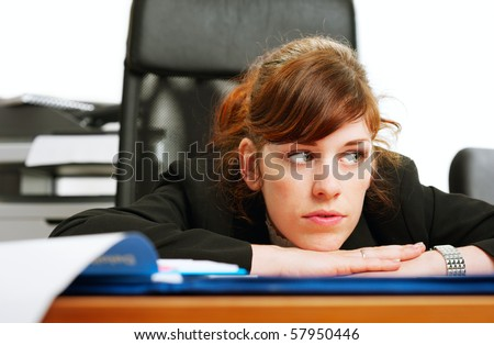 Close-up of a dissatisfied business lady at a  desk with her head resting on her hands