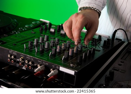 Close up of a DJ's mixing deck. Green gel over background light. - stock photo