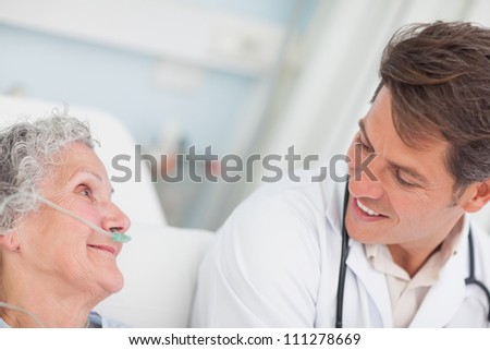 Close up of a doctor looking at a patient in hospital ward - stock photo