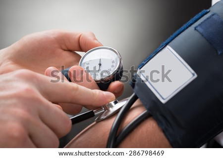 Close-up Of A Doctor's Hand Checking Blood Pressure Of A Patient
