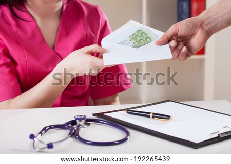Close-up of a doctor taking bribe, horizontal - stock photo