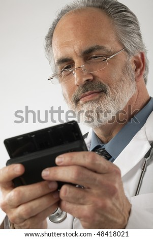Close-up of a doctor wearing glasses and a lab coat and texting on a cell phone. Vertical shot. - stock photo