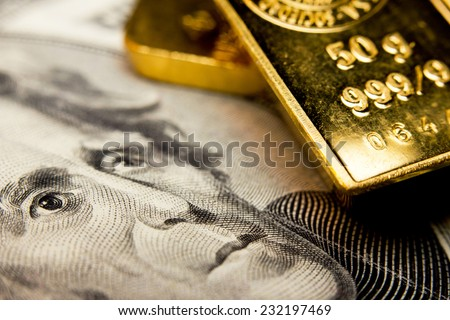 Close-up of a 20-dollar banknote (figuring president Jackson) and a gold bullion - stock photo