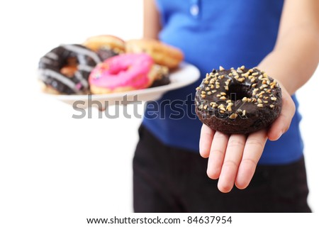 Close up of a donut on ladys' hand - stock photo