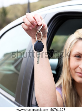 Close-up of a driver holding a key after buying a new car - stock photo