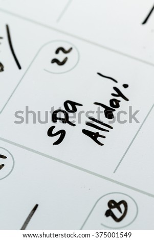 close up of a dry erase calendar with the words Spa and All day hand written on it - stock photo