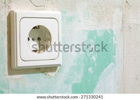 Close up of a electric socket, located on a green plasterboard - stock photo
