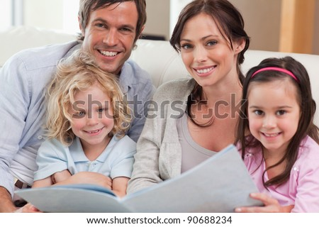 Close up of a family looking at a photo album in a living room - stock photo