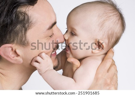Close up of a father holding his child and smiling at each other. - stock photo