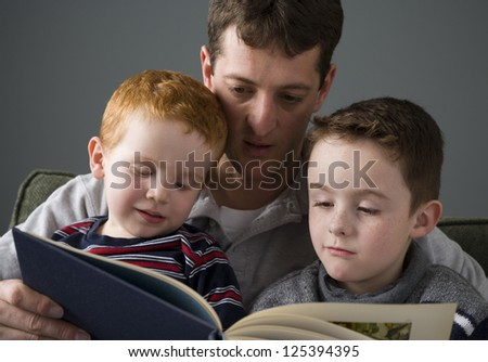 Close-up of a father reading book with his sons