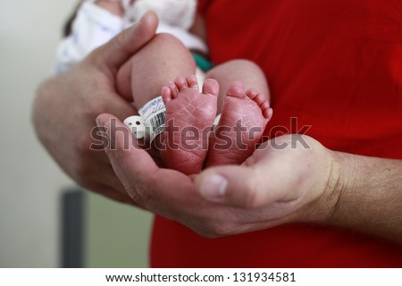 close up of a father's hand and babies feet, newborn. Maternity hospital - stock photo
